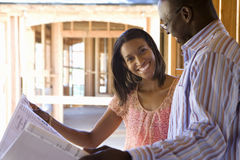 Young couple with blueprints in partially built house, smiling Royalty Free Stock Photo