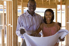 Young couple with blueprints in partially built house, smiling, portrait Royalty Free Stock Photo
