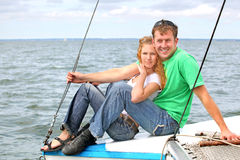 Young Couple on Boat. Young couple, man and woman, sitting on the edge of a boat Royalty Free Stock Photography