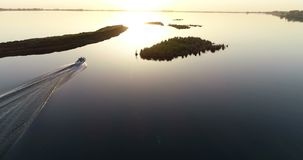 Young couple in the boat. On beautiful lake. Speed, sunset and love stock video footage