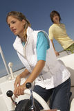 Young couple on boat with woman steering Royalty Free Stock Images