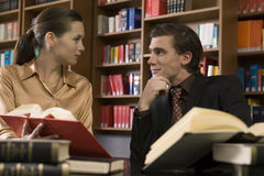 Young Couple With Books At Library Desk Stock Image