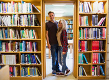 Young couple by bookshelves in the library Stock Photography