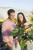 Young Couple At Botanical Garden. Happy young couple with potted plant at botanical garden Stock Image