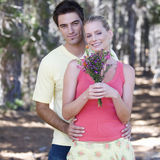 A young couple with a bouquet of flowers Stock Images