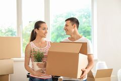Young couple with box and houseplant indoors. Moving into new house royalty free stock photo