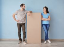 Young couple with box indoors. Moving into new house royalty free stock images