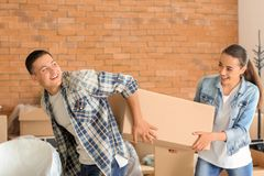 Young couple with box indoors. Moving into new house stock images
