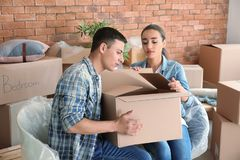 Young couple with box indoors. Moving into new house stock photography
