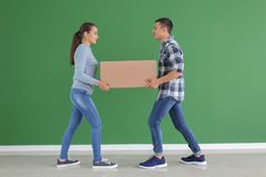 Young couple with box near color wall indoors. Moving into new house royalty free stock photos