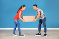 Young couple with box near color wall indoors. Moving into new house stock photos