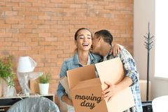 Young couple with box and vase indoors. Moving into new house royalty free stock photo