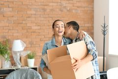 Young couple with box and vase indoors. Moving into new house royalty free stock photography