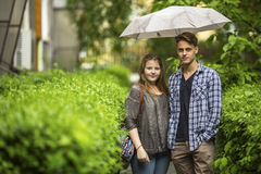 Young couple, boy and girl standing under an umbrella on the green track in the front yard near the house Stock Photo