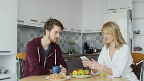Young couple during breakfast, man showing something on smartphone his girlfriend stock video