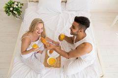 Young Couple Breakfast Sitting In Bed, Happy Smile  Hispanic Man And Woman Morning Top Angle View Royalty Free Stock Photography