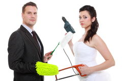 Young couple bride groom household chores isolated. Feminism emancipation concept. Humorous funny couple bride groom in domestic role, sharing household chores stock photo