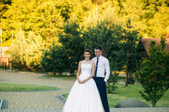Young couple, bride and groom walking and enjoying their wedding day. Sunshine. Summer. Royalty Free Stock Photo