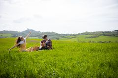 A young couple in bright clothes sitting on a bright green meadow and the man playing guitar while his happy girlfriend