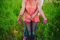 Young couple in bright spots of paint holding hands in nature, painters, repair, Holi festival Stock Photo