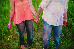 Young couple in bright spots of paint holding hands in nature, painters, repair, Holi festival Royalty Free Stock Photo