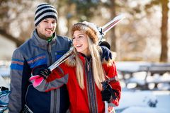 Young couple bring skis on shoulder. On winter holiday stock image
