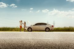 Young couple traveling on the car in sunny day. The young couple broke down the car while traveling on the way to rest. They are trying to fix the broken by stock photos