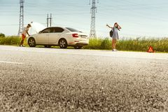 Young couple traveling on the car in sunny day. The young couple broke down the car while traveling on the way to rest. They are trying to stop other drivers and royalty free stock image