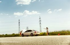 Young couple traveling on the car in sunny day. The young couple broke down the car while traveling on the way to rest. They are trying to stop other drivers and stock images
