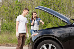 Young couple broken down at the side of a road Royalty Free Stock Image