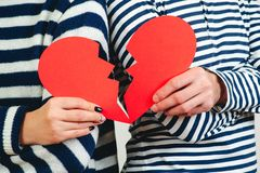 Young couple with broken heart, close up. Unrequited love. Broken heart. Love and relationship problems concept. Man and woman. Hands holding two parts of royalty free stock image