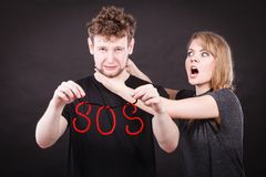 Young couple with broken heart and sos word. Betrayal and break up in relationship. Young couple arguing and holding red sos word sign symbol. Blonde women in royalty free stock images