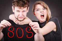 Young couple with broken heart and sos word. Betrayal and break up in relationship. Young couple arguing and holding red sos word sign symbol. Blonde women in stock photography