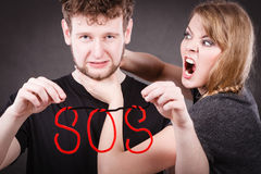 Young couple with broken heart and sos word. Betrayal and break up in relationship. Young couple arguing and holding red sos word sign symbol. Blonde women in stock image