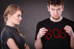 Young couple with broken heart and sos word. Betrayal and break up in relationship. Young couple with big plaster broken heart and red sos word sign symbol Stock Images