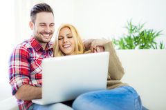 Young couple browsing internet at home, using laptop and smiling Royalty Free Stock Image