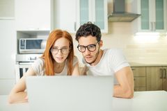 Couple browsing internet together sitting at table and smiling and read screen. Young couple browsing internet together sitting at table and smiling happily as Royalty Free Stock Photos