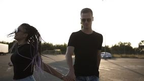 Young couple - brunette dreadlocks girl in sunglasses and her boyfriend walking, holding hands. Sun shines on the stock video