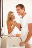 Young Couple Brushing Teeth In Bathroom Stock Image