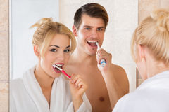 Young Couple Brushing Teeth In Bathroom. Young Smiling Couple Looking At Mirror Brushing Teeth Together In Bathroom At Home stock photography