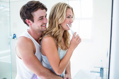 Young couple brushing their teeth at home. In the bathroom stock photo
