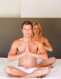 Young couple on buddha position on bed Royalty Free Stock Photography
