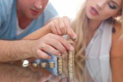 Young couple buildin growing euro columns Stock Photos