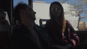 Young couple is on the bus. Cheerful bus commuters. Young couple talking during the ride in the city stock video footage
