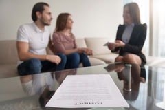 Young couple and businesswoman discussing deal, focus on contrac Stock Photo