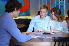 Young couple buy apartment with realtor contract. Young business rich couple buy an apartment, property, house, apartment, enter into a contract with a realtor Royalty Free Stock Photography