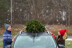 Couple with their Christmas tree on roof of the car Royalty Free Stock Photos
