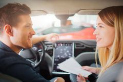 Young couple buying first electric car in the showroom. Attractive family talking about car purchase in the cabin of stock photo