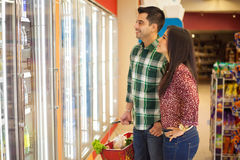 Young couple buying frozen food. Portrait of a young beautiful couple in front of a few refrigerators and buying some frozen food royalty free stock images