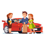 Young couple buying or renting new red car. Couple buying or renting new red car. Saleswoman selling automobile and giving keys to family. Man and woman standing Stock Photography